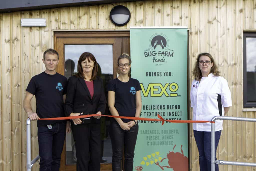 Photograph of Minister for Environment, Energy and Rural Affairs Lesley Griffiths AM cutting a ribbon to officially open the Bug Farm Foods R&D facility